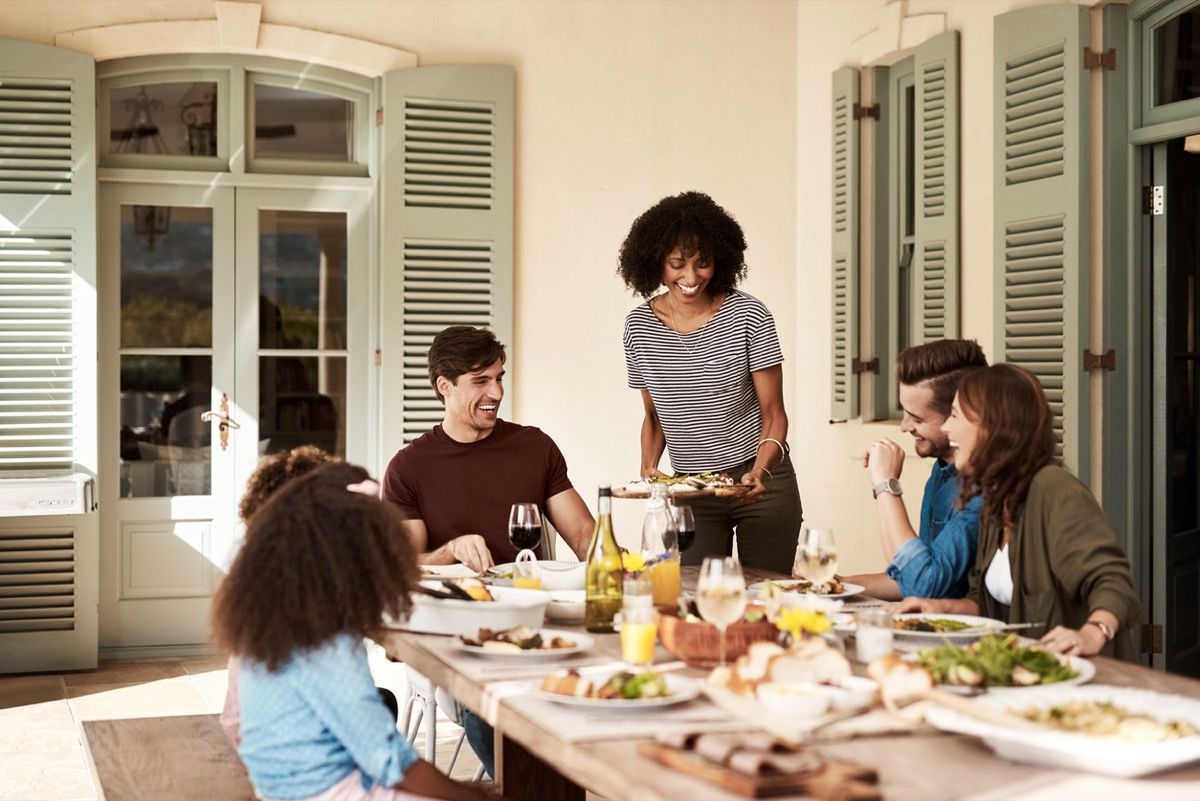black woman serving food to family and friends at outdoor table
