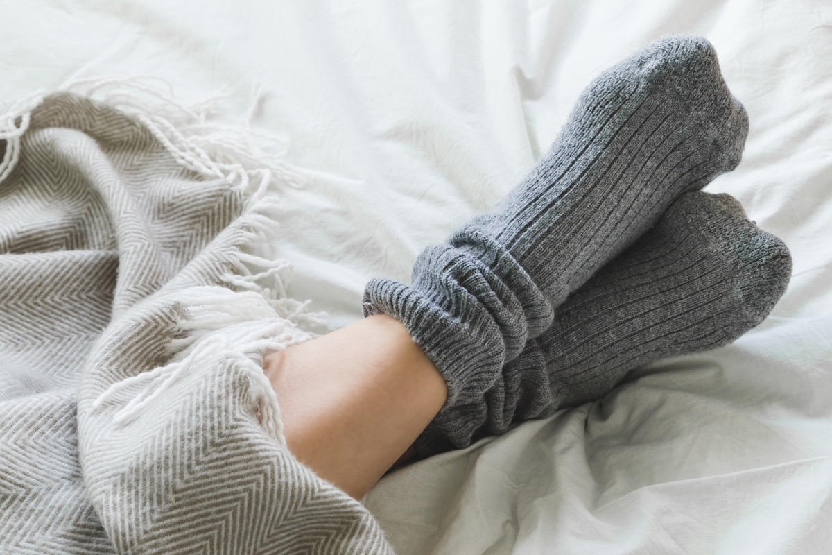 close up of crossed feet with socks on under a blanket in bed