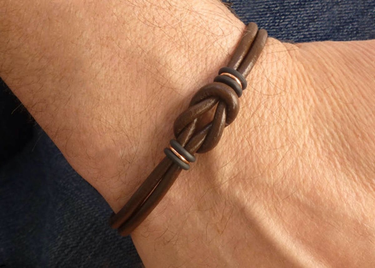 white man's wrist with brown leather bracelet