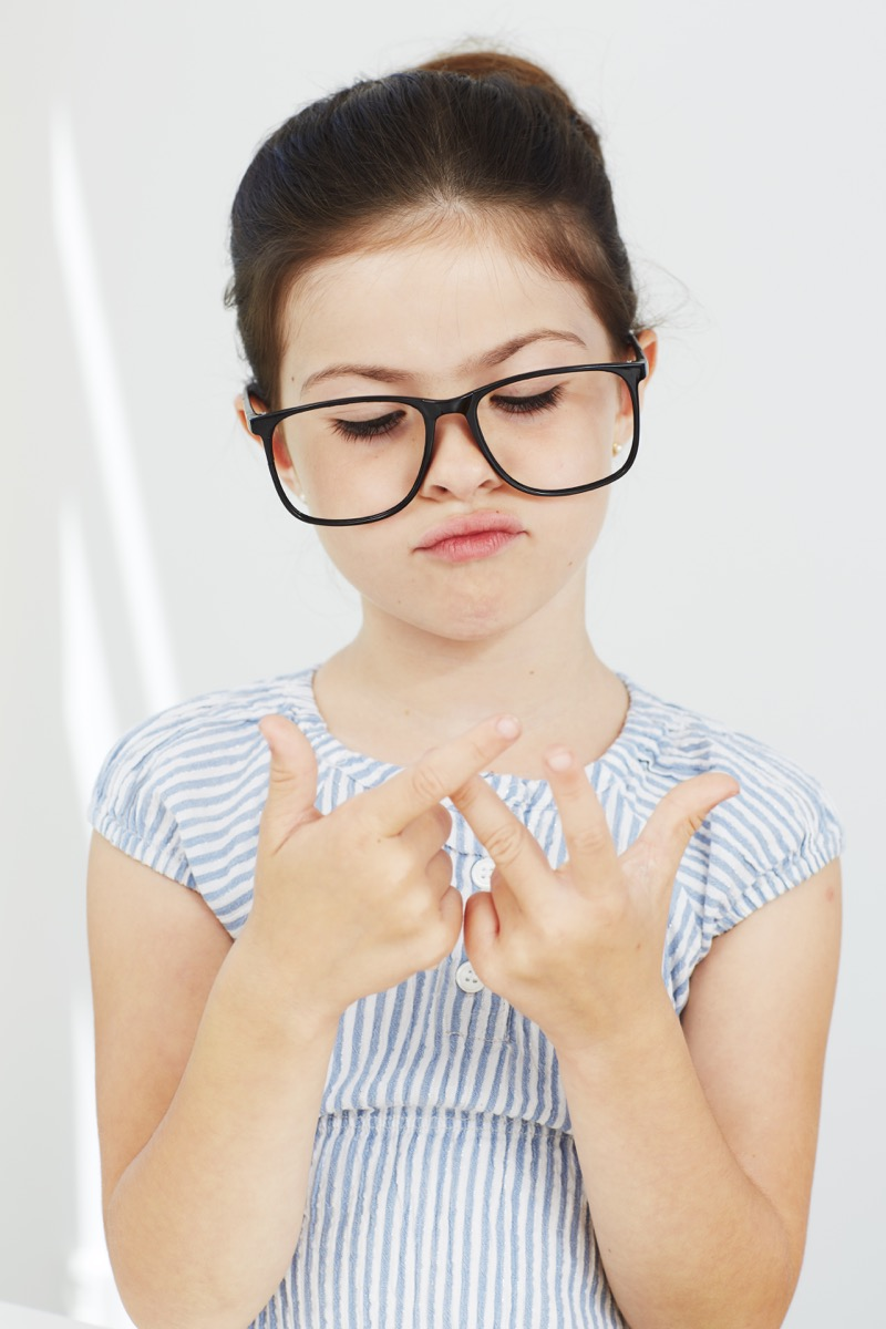 Little girl counting on her fingers wearing glasses