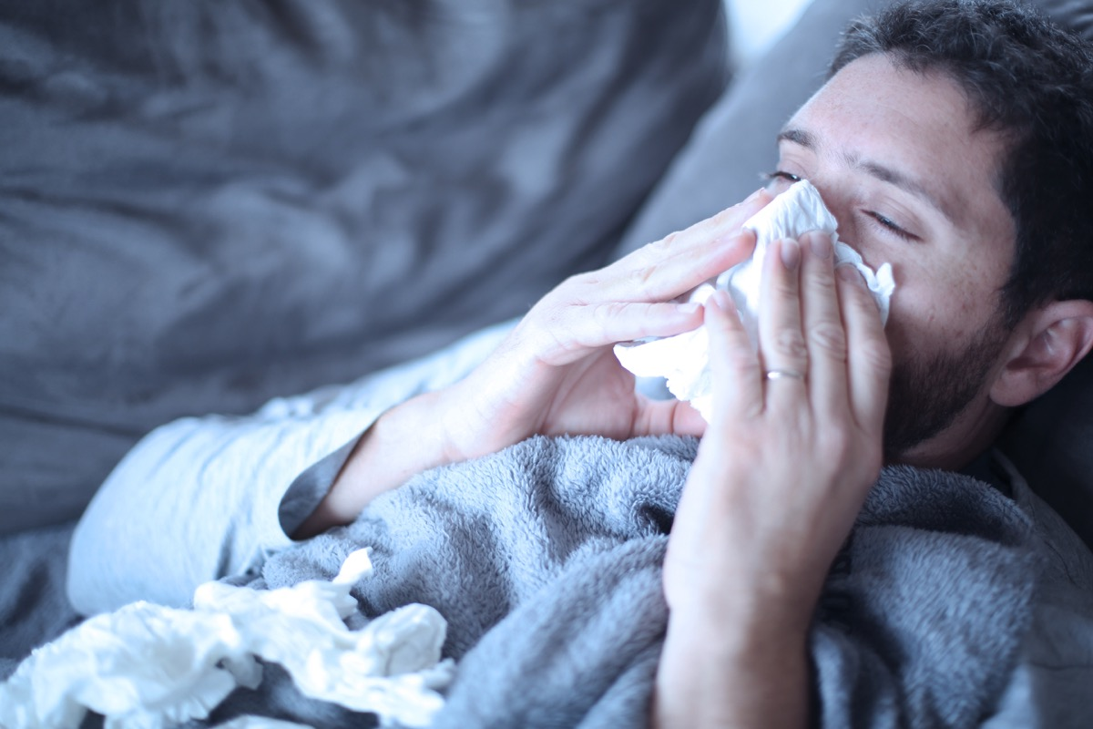 man blowing his nose on the couch body changes over 40