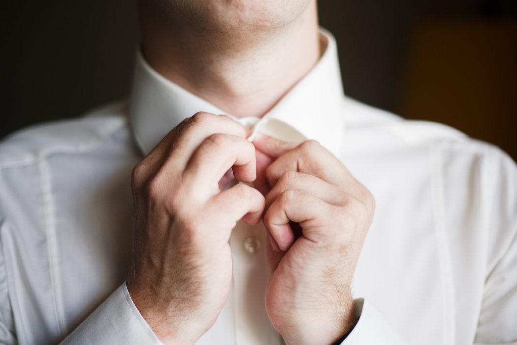 Man Buttoning Dress Shirt Surprising Features on Your Clothes