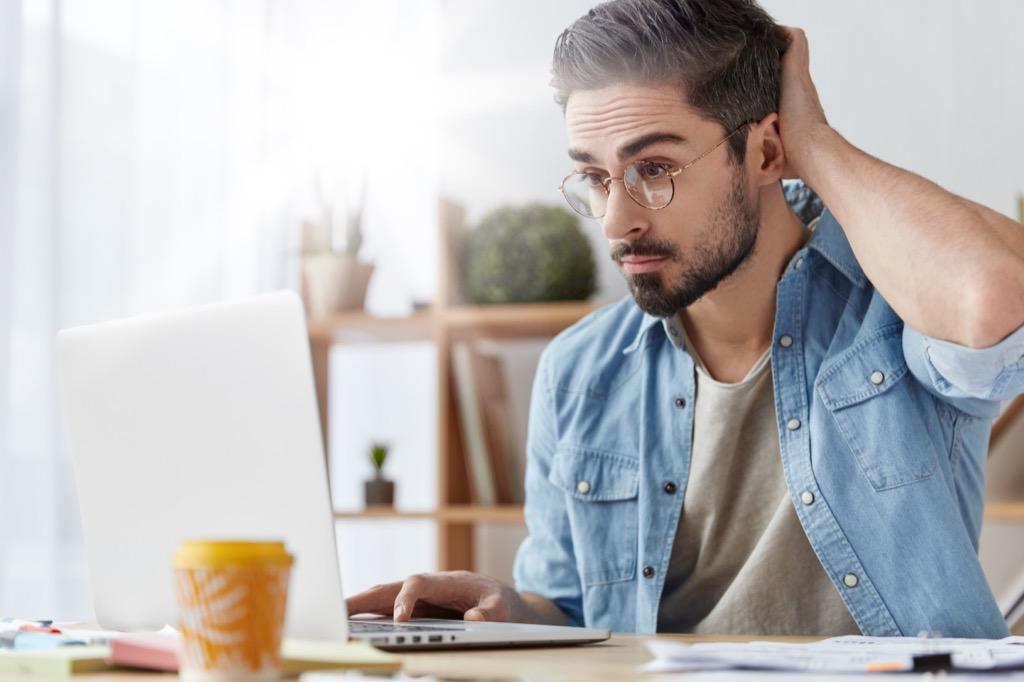 man fidgeting in front of a laptop