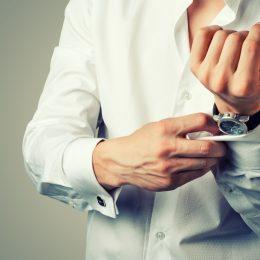 white man wearing watch putting on cufflinks