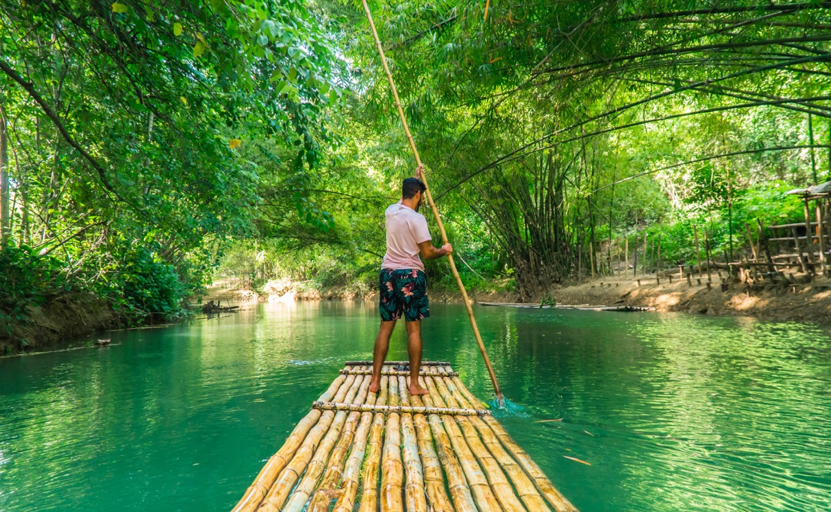 Man stand up paddling on a raft down a river