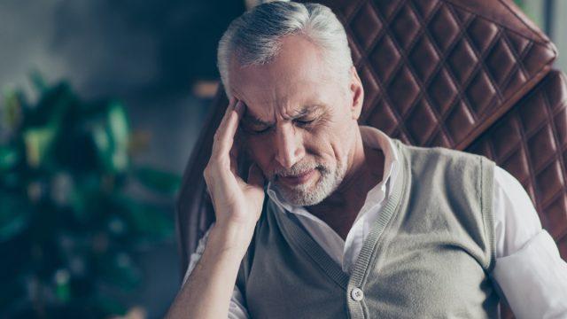 man sitting in an armchair suffering from a headache - what causes headaches