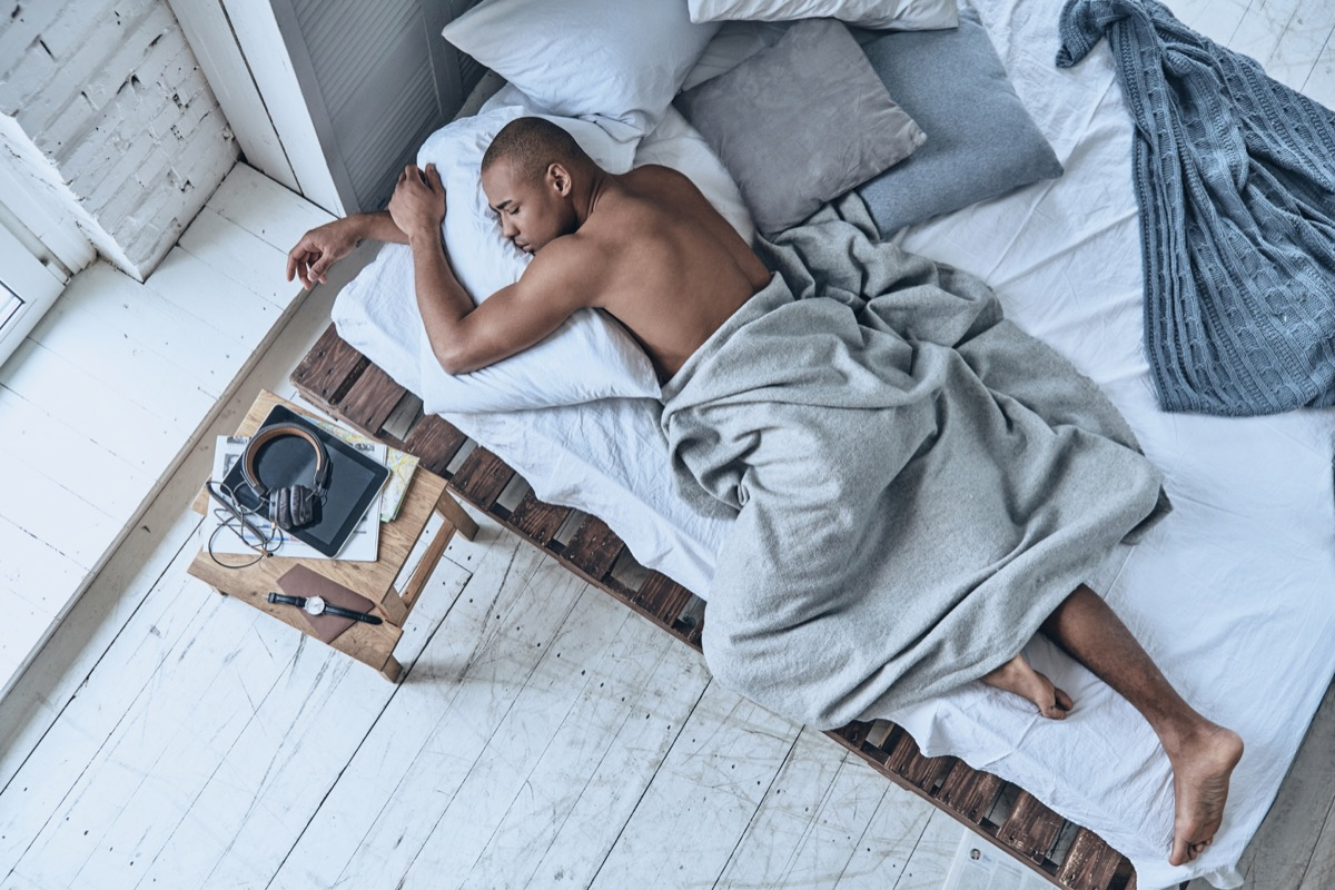 man sleeping on his stomach with his arms wrapped around a pillow - sleeping positions