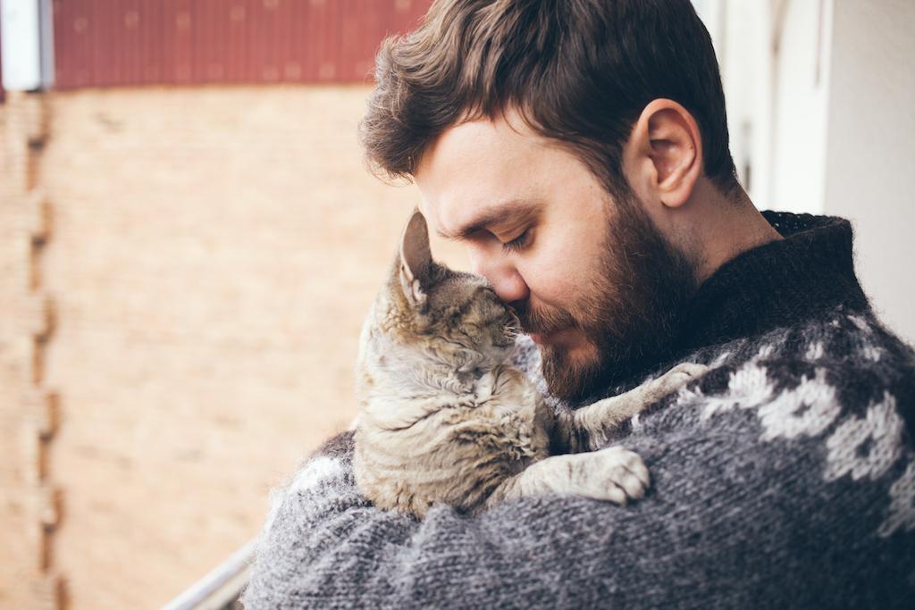 man cuddling his pet cat