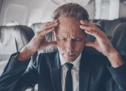 businessman on an airplane suffering the side effects of flying
