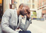 man holds head, health risks for men over 40
