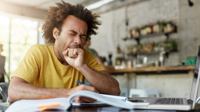 man doing work at a kitchen table and yawning lies over 40