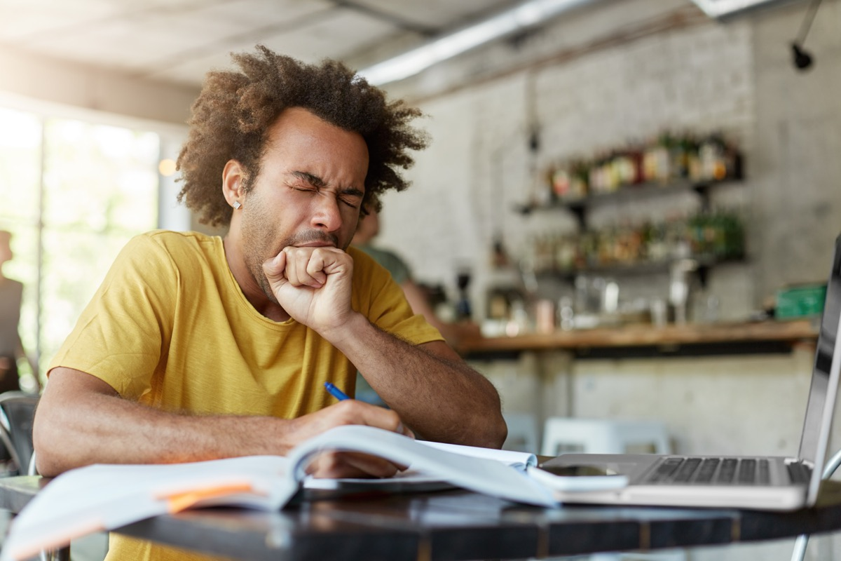 man doing work at a kitchen table and yawning - why do we yawn