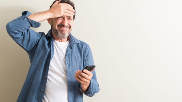 middle aged man using smartphone stressed with hand on head