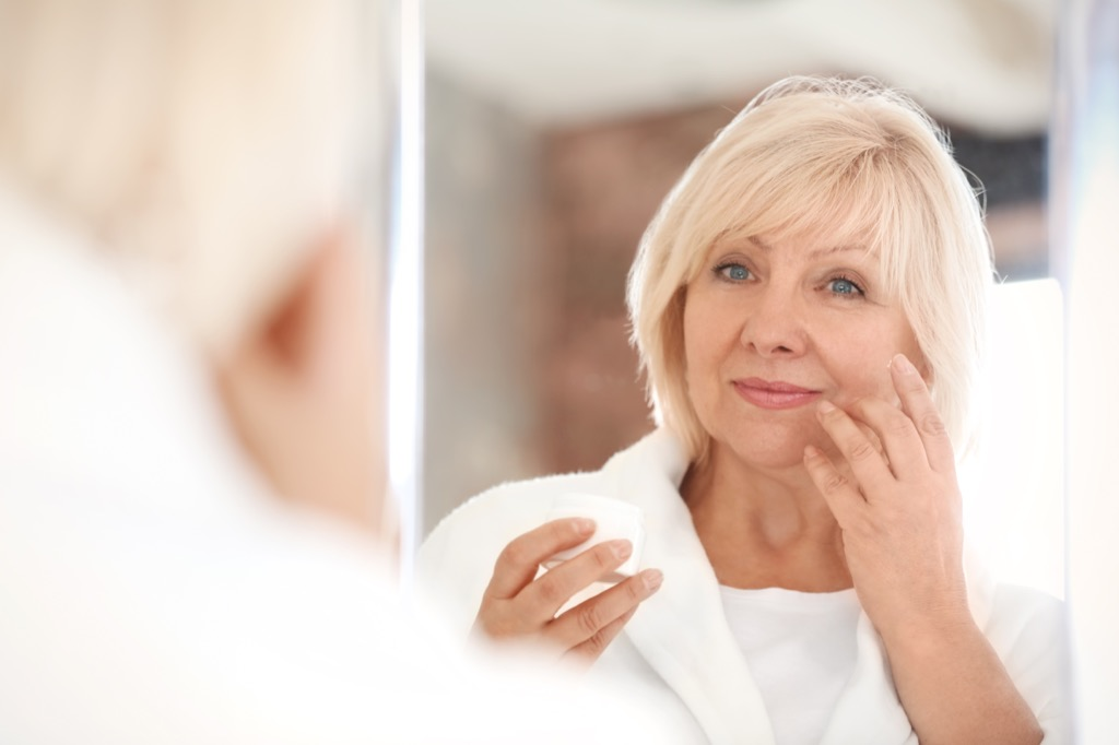 middle aged woman looking in a mirror