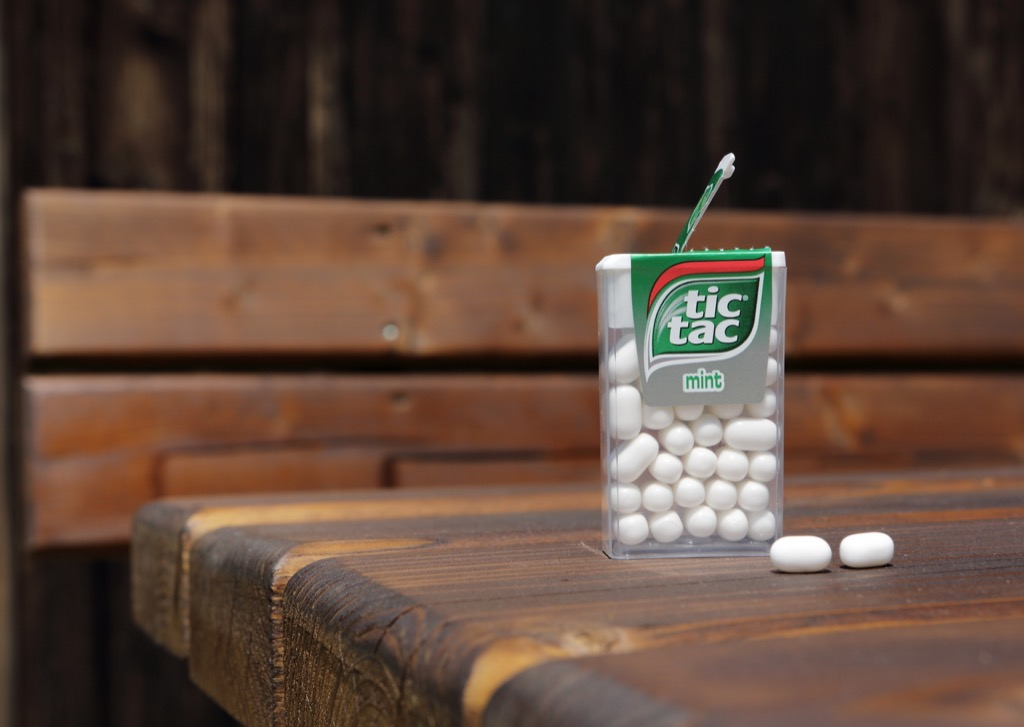 an open mint white tic tac box resting on a wooden table