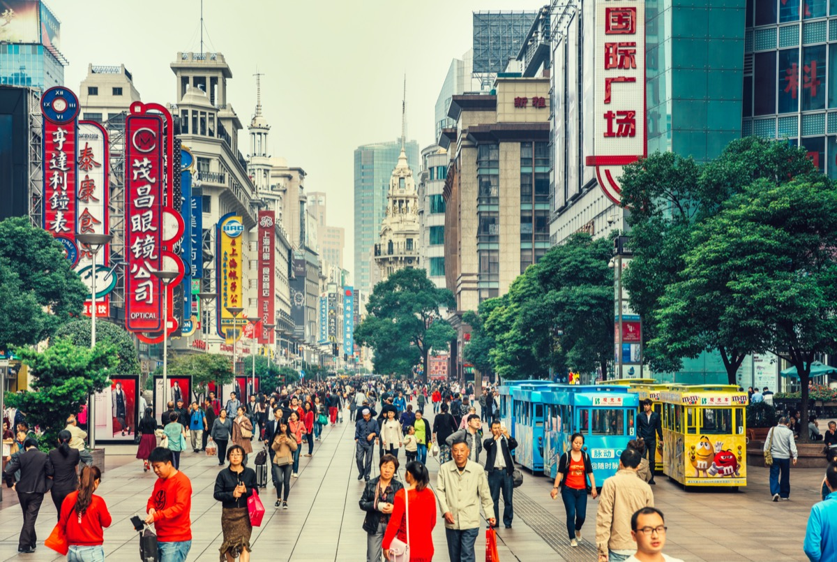 Crowds walk below neon signs on Nanjing Road. The street is the main shopping district of the city and one of the world's busiest shopping districts.