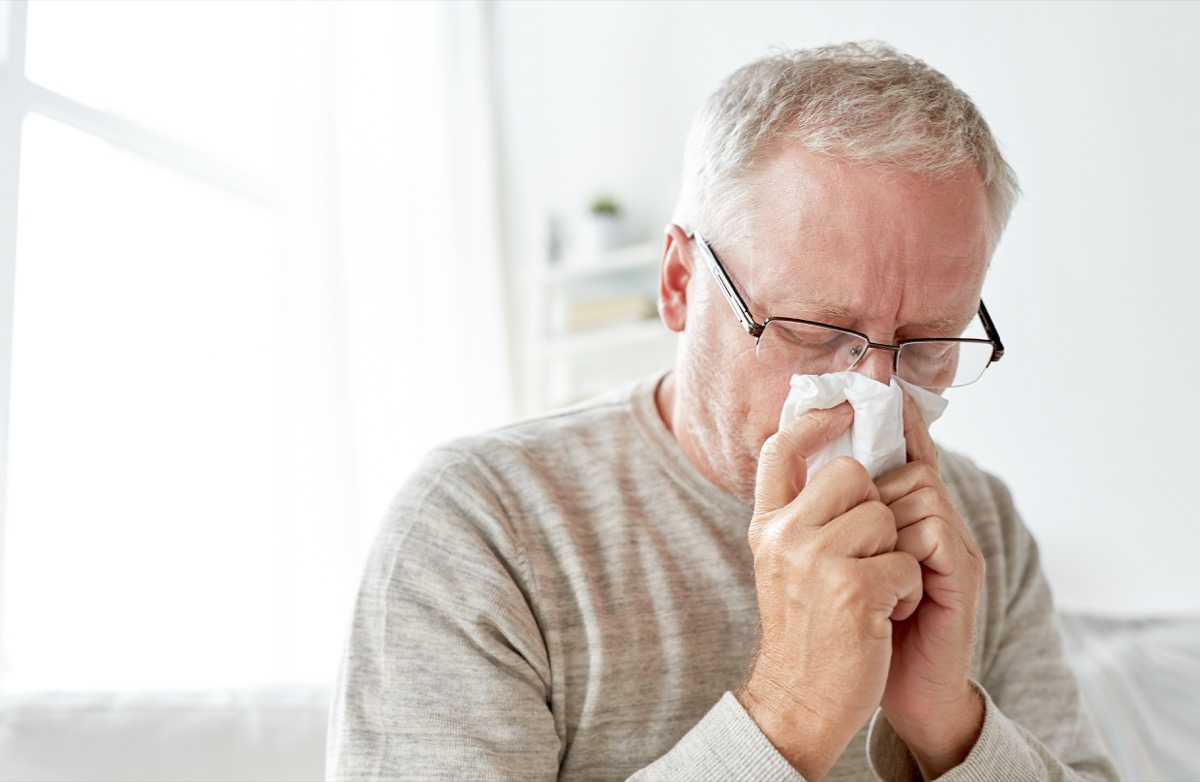 Older man with a cold blowing his nose into a tissue
