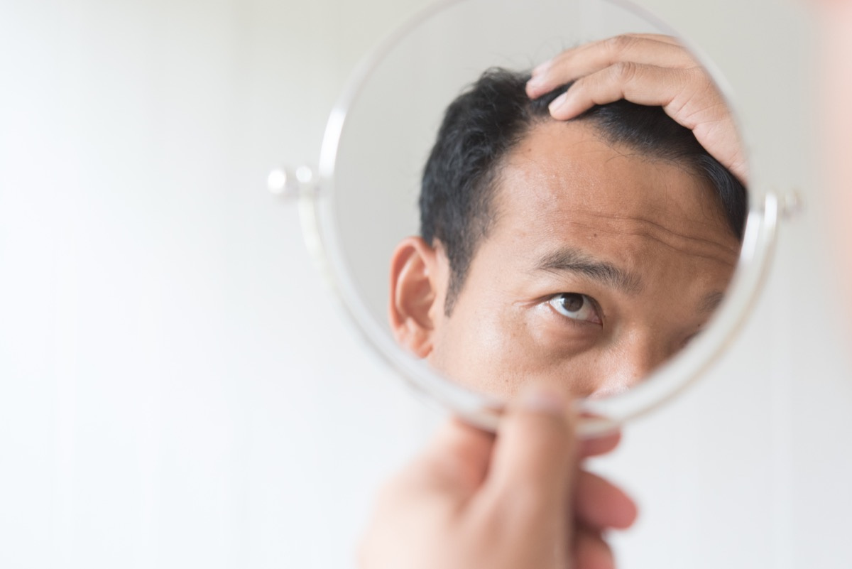 older man looking in mirror at hair loss men's health concerns over 40