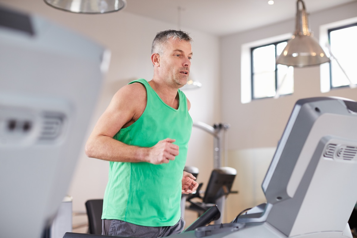 Mature white man running and doing cardio on the treadmill