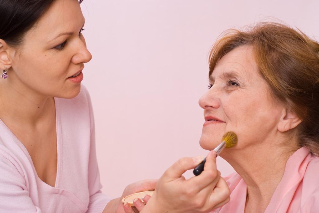 older woman having makeup applied, look better after 40