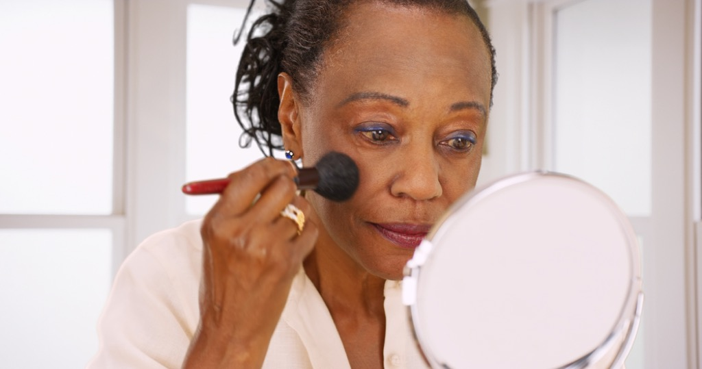 older woman putting on makeup, look better after 40