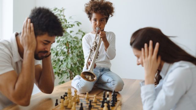 a daughter playing trumpet interrupting mom and dad playing chess