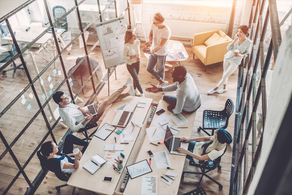 an overhead shot of office employees in a glass-walled conference room