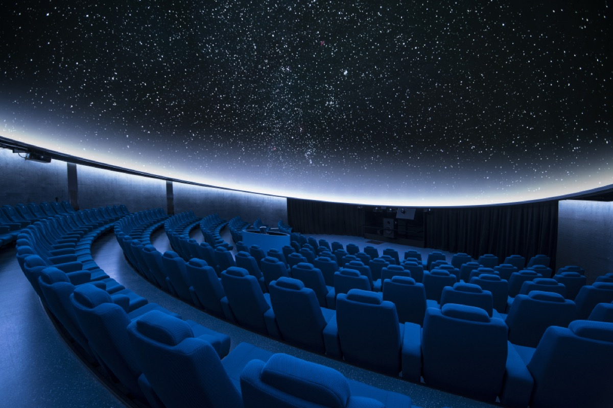 interior of planetarium shows empty seats with stars projection