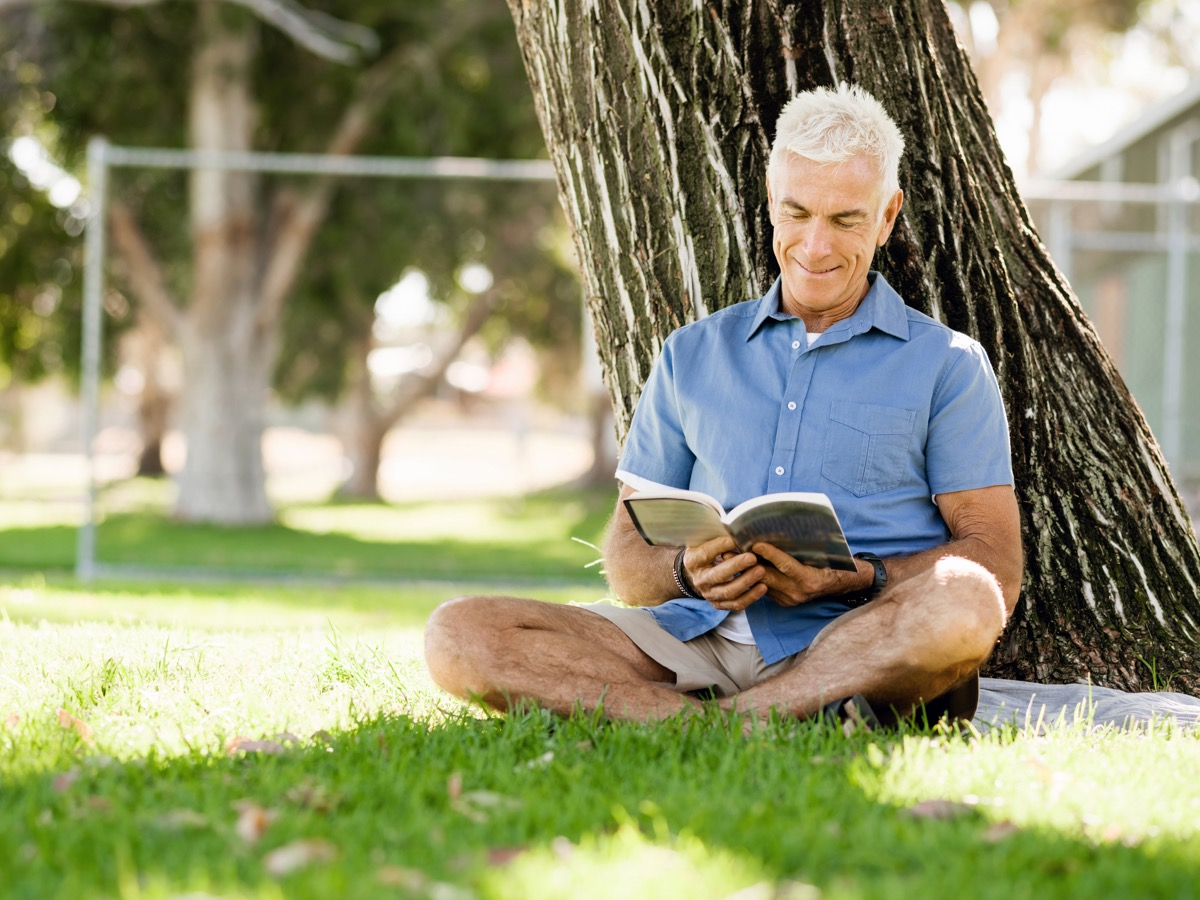 man reading by a tree at the park