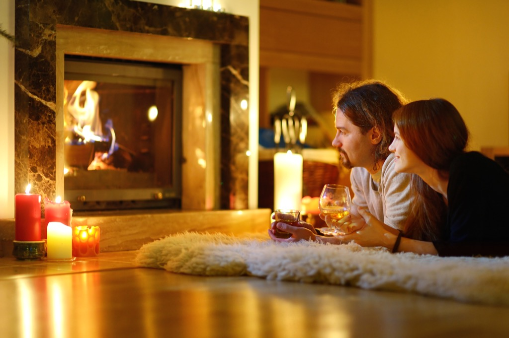 couple by the fireplace and candles at home, date night ideas