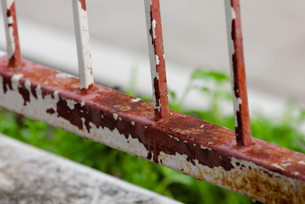 rusty porch railing with chipping white paint