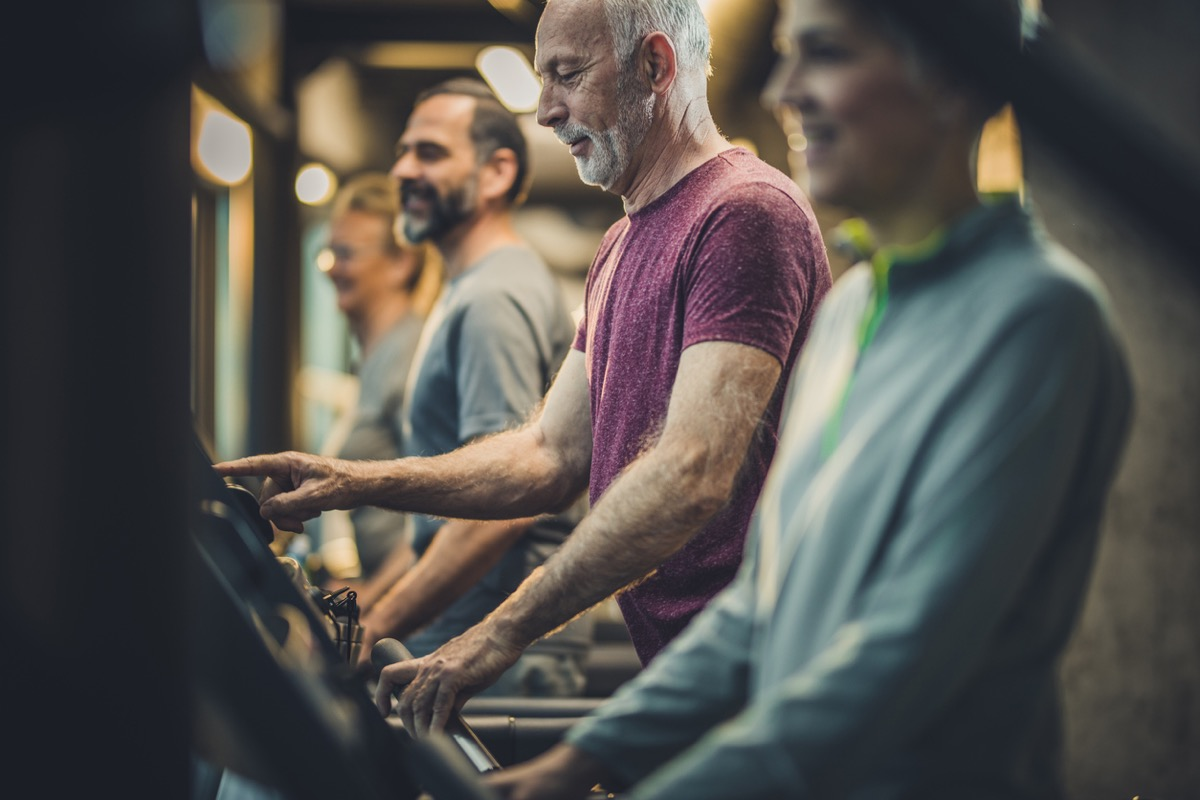 Group of athletic senior exercising on treadmills at the gym
