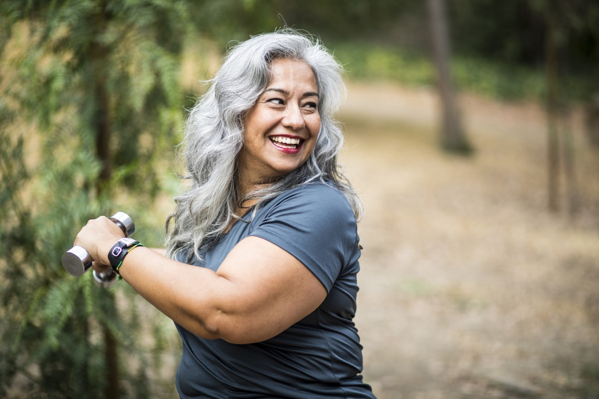 Senior Mexican Woman working out and stretching with weights in nature