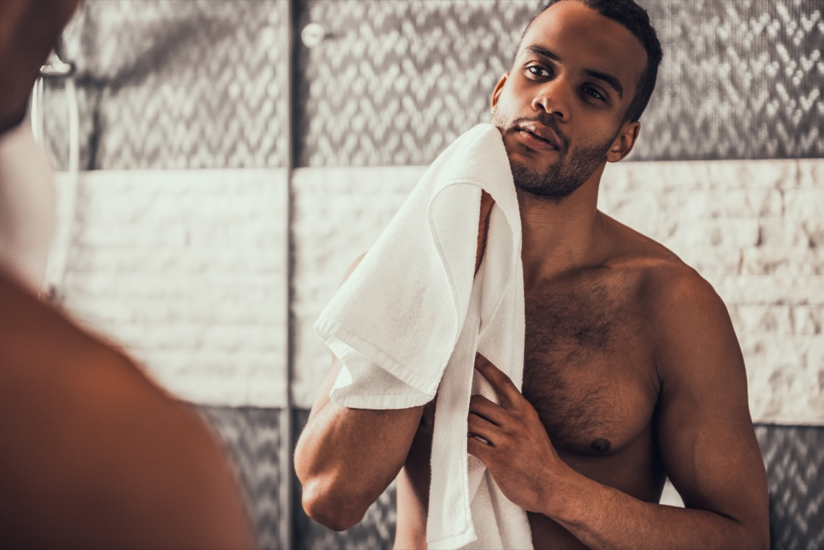 a shirtless man holding a towel looking in the mirror, things you should clean every day