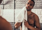 a shirtless man holding a towel looking in the mirror, relationship white lies
