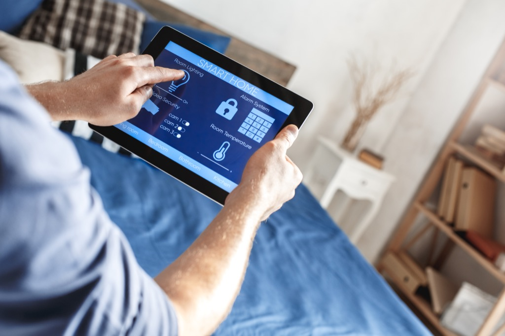 Pria yang mengutak-atik sistem keamanan rumah pintar di tablet