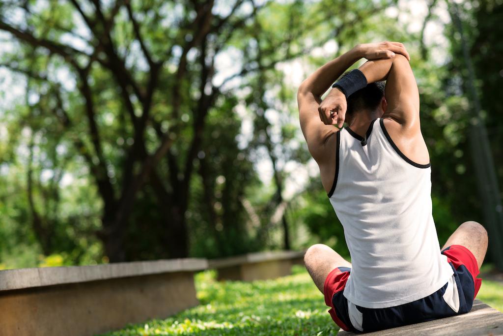 man stretching with a sweatband on his wrist ways to de-stress