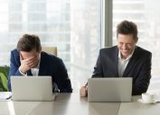 two guys at laptops laughing at anti-jokes