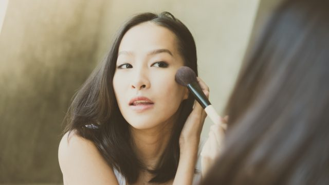 woman putting on makeup, working mom