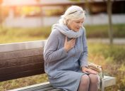 older woman sits on bench clutching chest, what your indigestion means