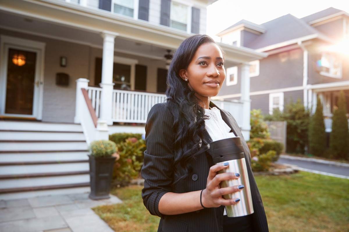 Black businesswoman drinking coffee in a to-go cup on her way to work