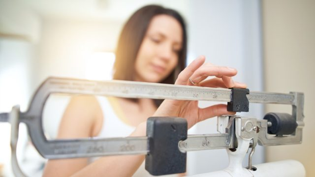 Shot of a young woman weighing herself on a scale