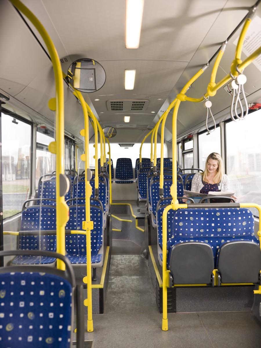 Woman reading a paper on an empty bus