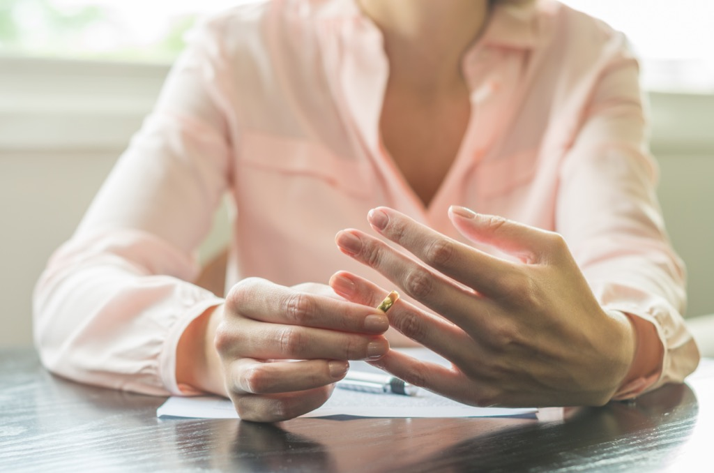 woman taking off a wedding ring sitting at a table going over divorce paperwork