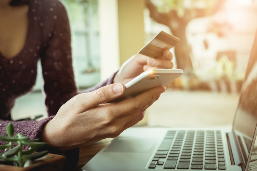 woman sitting in front of a laptop using a credit card to buy something on her smartphone
