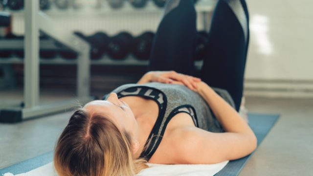 Woman at the Gym with Hand on Stomach - breathing problems