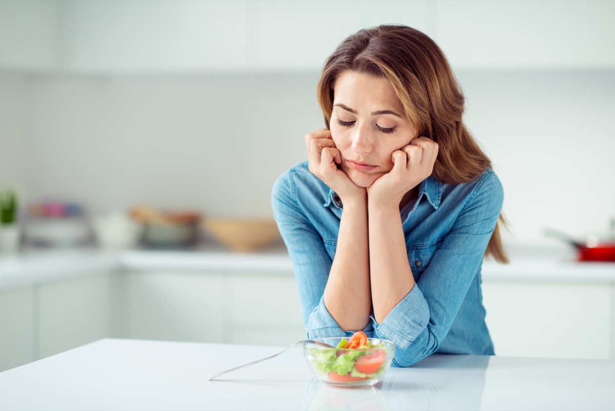 middle aged woman looks disappointed at small salad while standing in kitchen