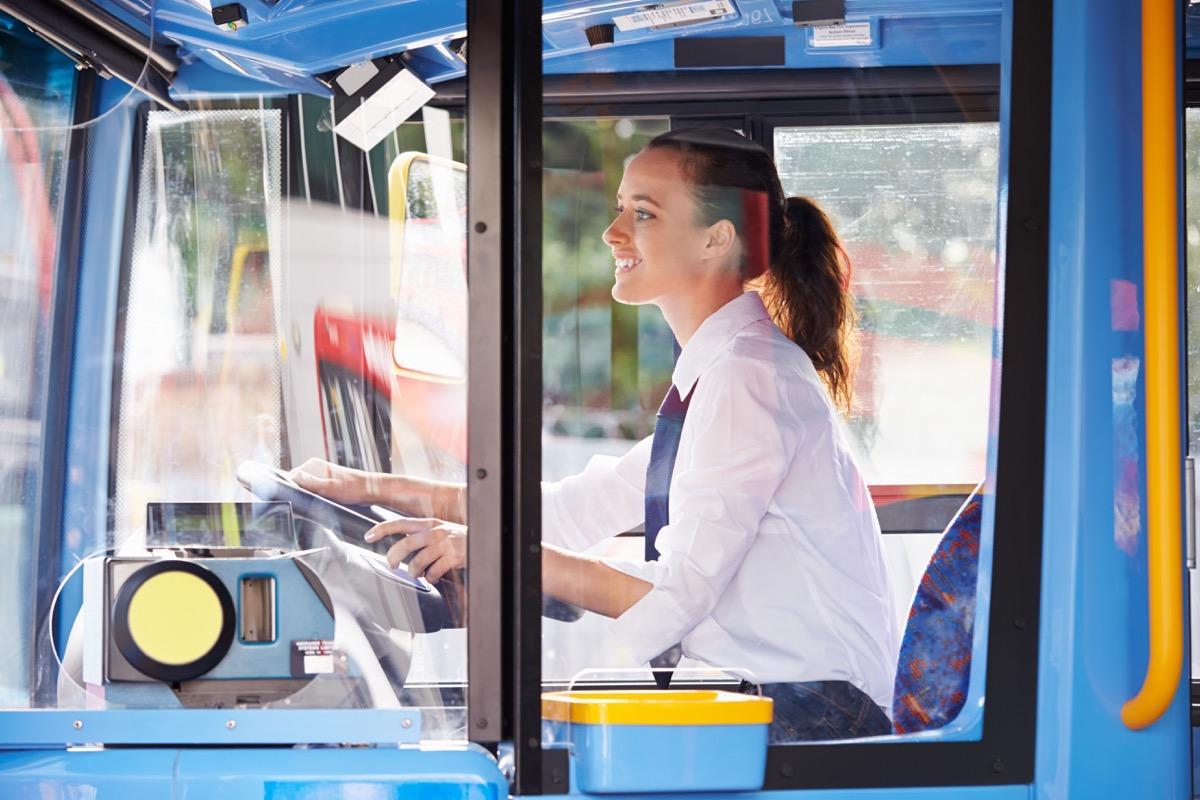 Young woman driving a public transportation bus