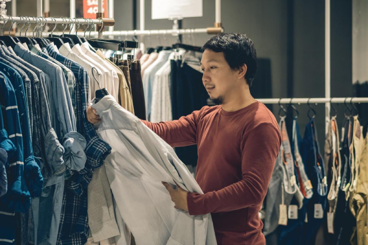 asian man looks at shirt while shopping