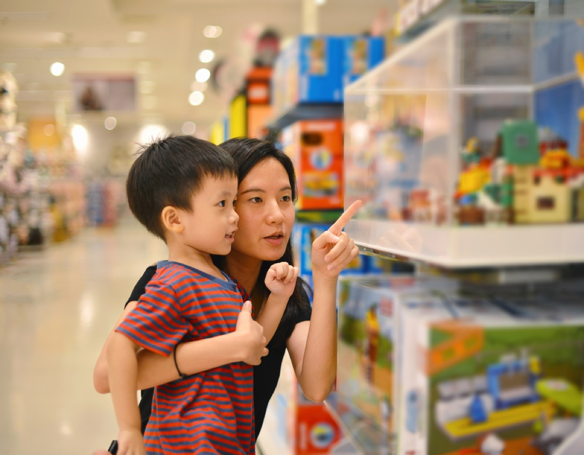 asian mom and son shop at toy store